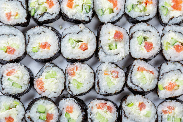 Homemade sliced Maki rolls with salmon, avocado and cucumber. Top view