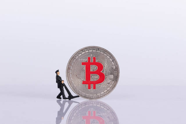 Miniature delivery worker with silver Bitcoin coin