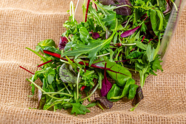 Salad mix and arugula on a background of burlap