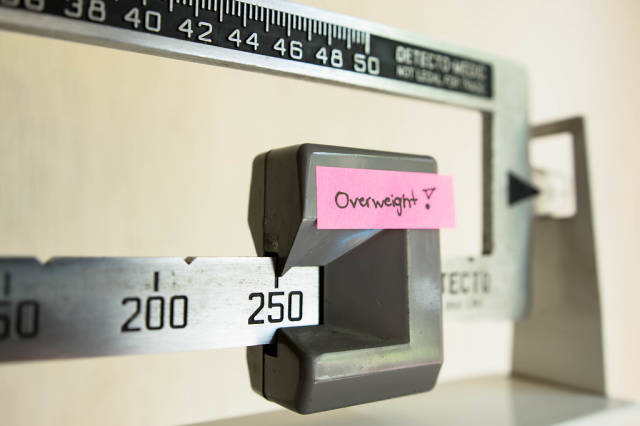 Doctor scale showing 250 pounds as OVERWEIGHT