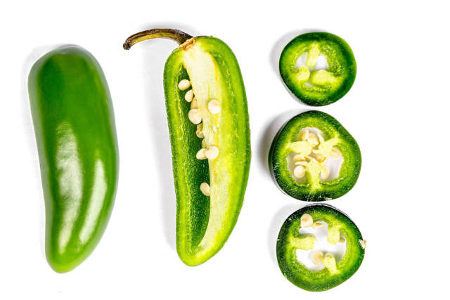 Jalapeno pepper halves and slices on a white background, top view