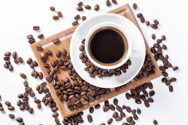Cup of coffee on a wooden kitchen board with grains