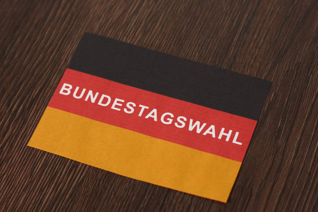 """Deutschland 2021: deutsche Flagge mit Schrift """"Bundestagswahl"""" auf einem hölzernen Tisch"""