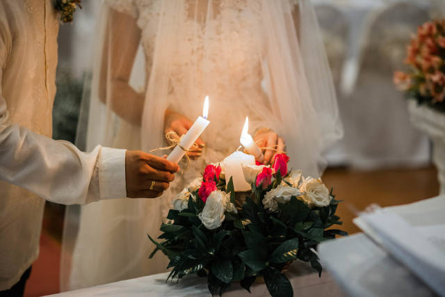 The couple lighting a unity candle at a wedding