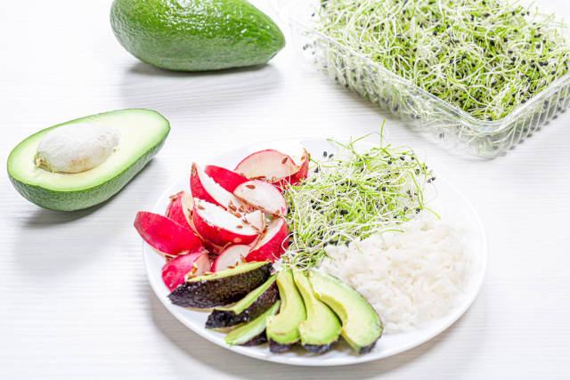 A plate of rice, radish, avocado and micro-greens onions on a white wooden background