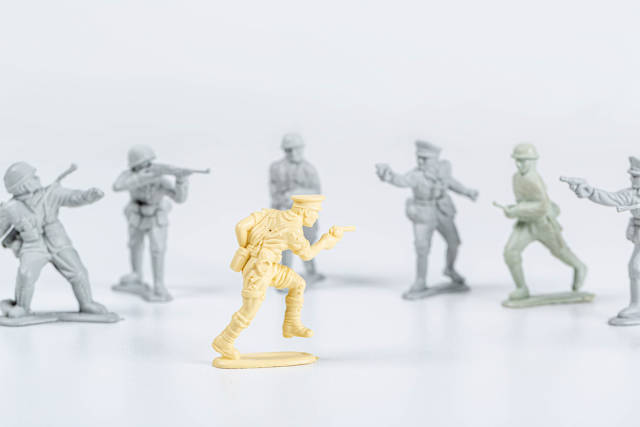 One yellow plastic toy soldier and many gray toy soldiers. Unequal power concept