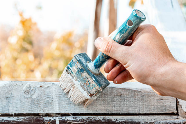Close up of a brush with white paint in the hand of a man