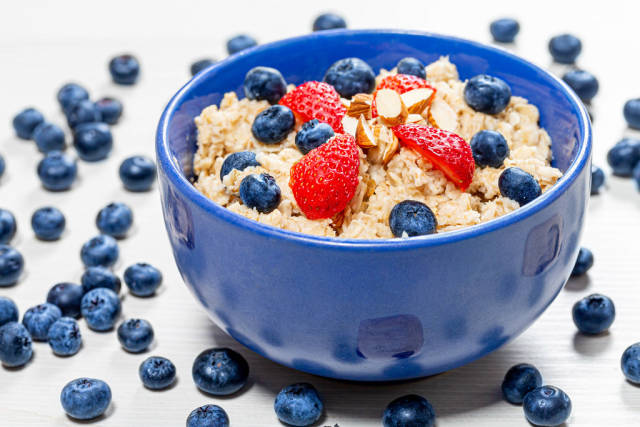 Oatmeal with fresh blueberries, almonds and strawberries in a blue bowl (Flip 2019)