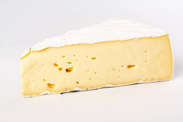 Piece of brie cheese on white background