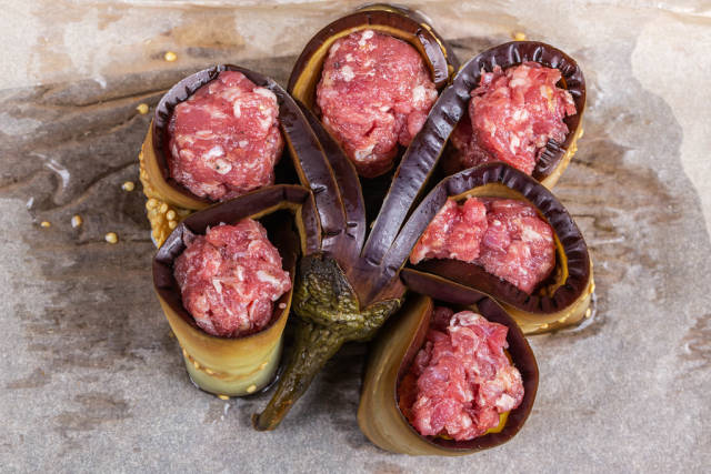 Eggplant stuffed with minced meat on parchment is prepared for baking