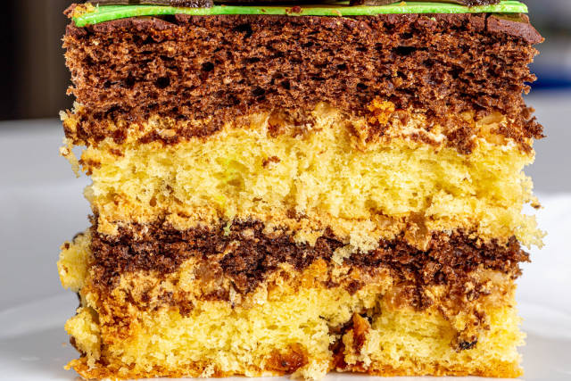 Close-up of a piece of sponge cake with yellow and chocolate biscuits