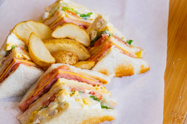 Close up of clubhouse sandwich with potato wedges