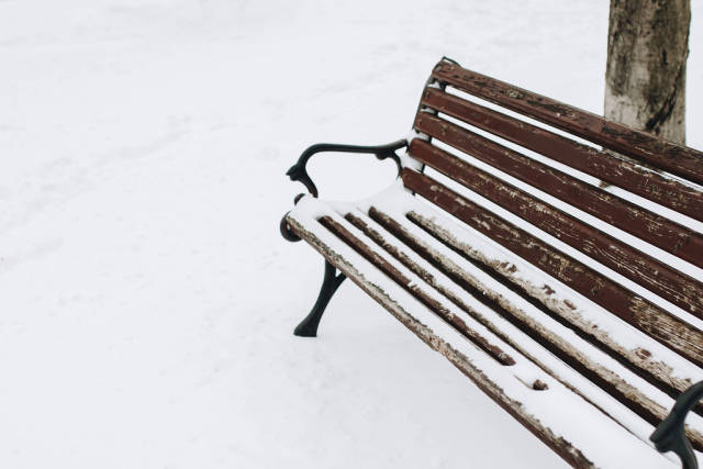 Outdoor shot of wooden bench covered with snow. Winter.