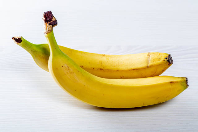 Two ripe bananas on a white wooden table