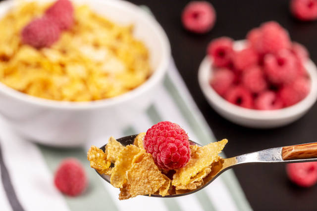 Close-up of cornflakes and raspberries in a spoon