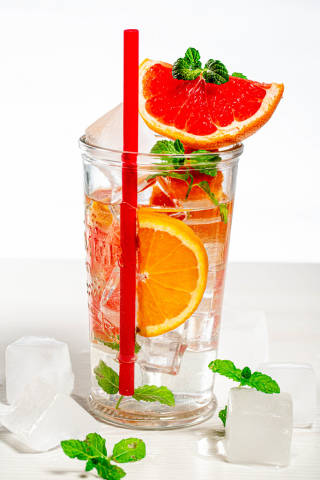 A glass of cold citrus lemonade with fresh fruit