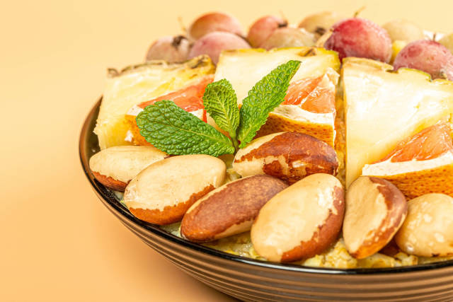 Close-up, porridge with brazil nuts, fruit and mint leaves in a black bowl