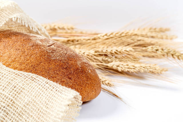 Black bread with spikelet wheat and burlap on white background
