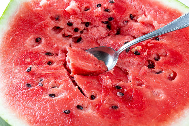 Ripe cut watermelon with seeds and spoon