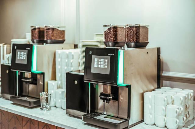 Weiße Tassen neben Kaffeemaschinen mit Kaffeebohnen