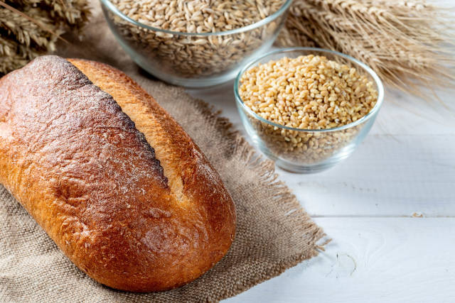 Bread with wheat and spikelets on a white wooden table