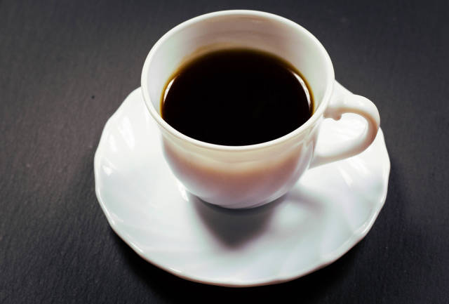 Cup of coffee against black background