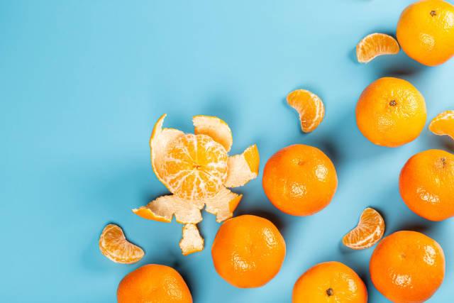 Fresh ripe tangerines on blue background