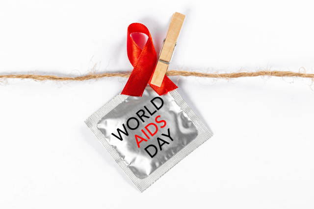 Aids awareness sign red ribbon and a condom