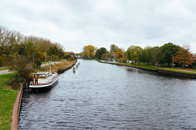 View of the Dutch canal with windmill near De Nieuwe Noorder park