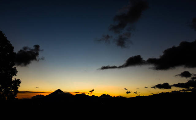 Wide view of colorful sunset behind Guatemalas volcanoes