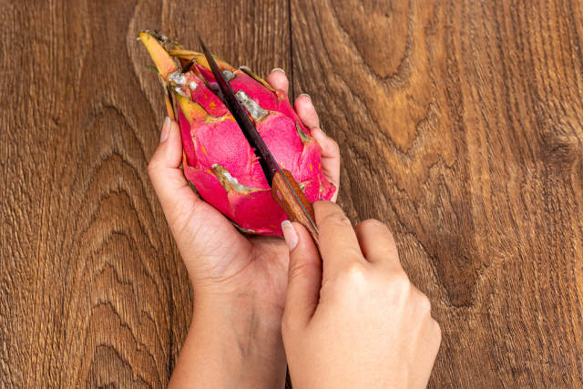Woman cuts a pitahaya fruit with a knife