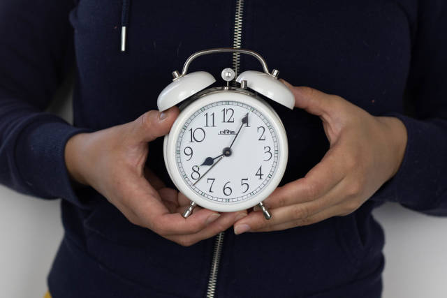Girl holds alarm clock