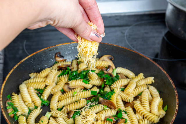 Female hand adds cheese to a pasta pan
