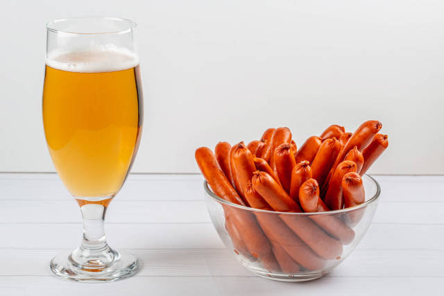 A glass of beer and smoked sausages in a bowl