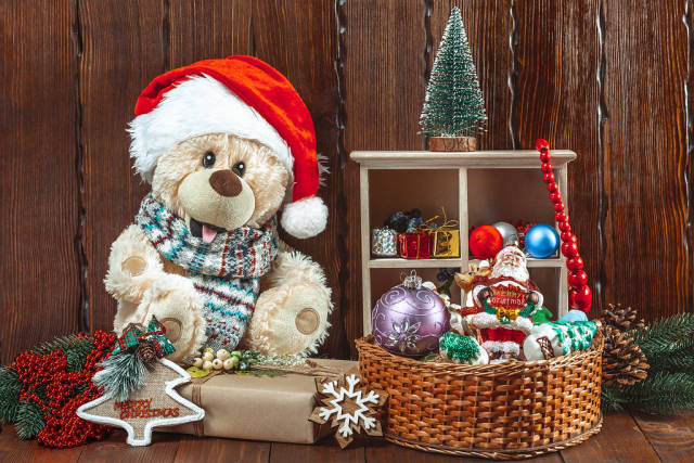 Christmas background with a teddy bear, Christmas toys and gifts on a wooden table. The concept of a childrens holiday, family celebration