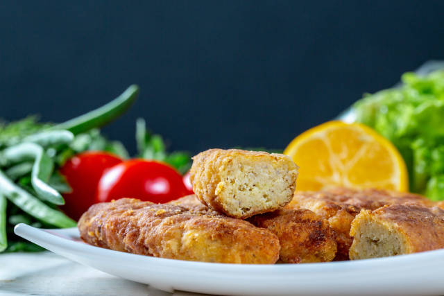 Fish sticks in breadcrumbs on a plate with vegetables