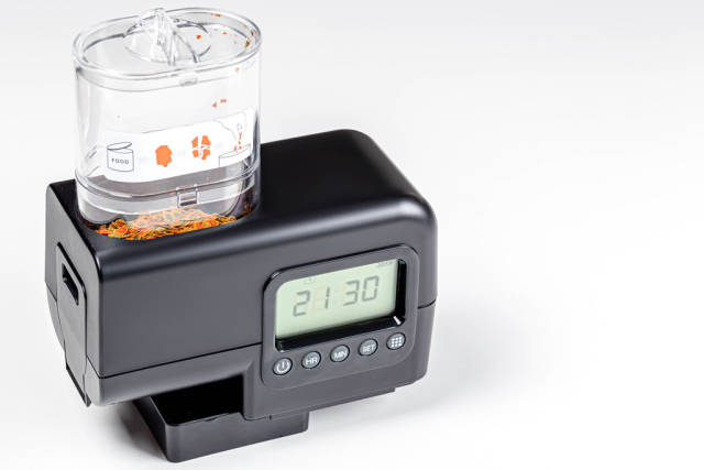 Fish feeder for aquarium with food on a white background