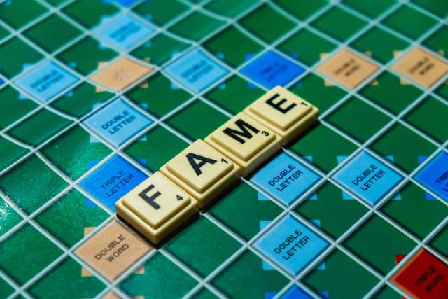 """Macro shot of """"Fame"""" word on scrabble board"""