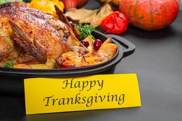 Happy Thanksgiving Essen mit ganzem gebackenem Hähnchen und Kürbisdekoration im Hintergrund