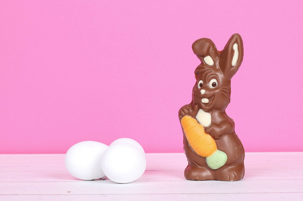 Chocolate bunny with Easter eggs and pink background