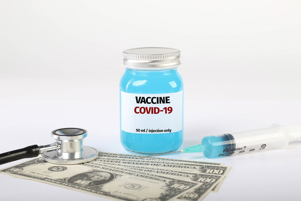 Covid-19 vaccine with money, stethoscope and syringe on white background