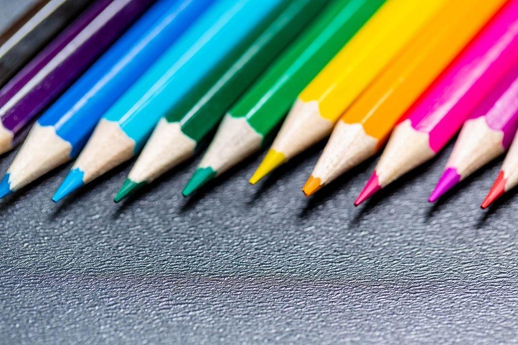 Nahaufnahme von Buntstiften, aufgereiht in Regenbogenfarben vor schwarzem Hintergrund