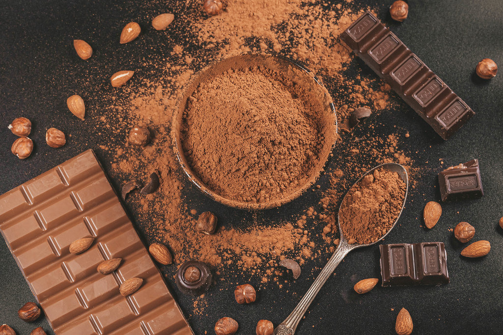 Milk and dark chocolate on a black background with nuts and cocoa, top view