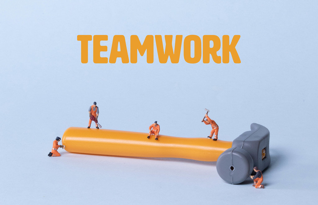 Hammer with miniature workers and Teamwork text