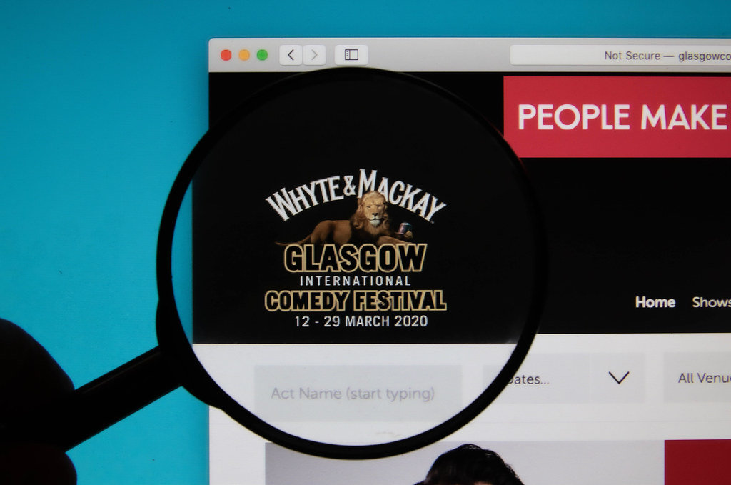 Glasgow International Comedy Festival logo on a computer screen with a magnifying glass
