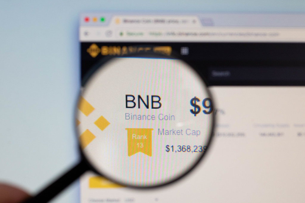 Binance Coin logo on a computer screen with a magnifying glass