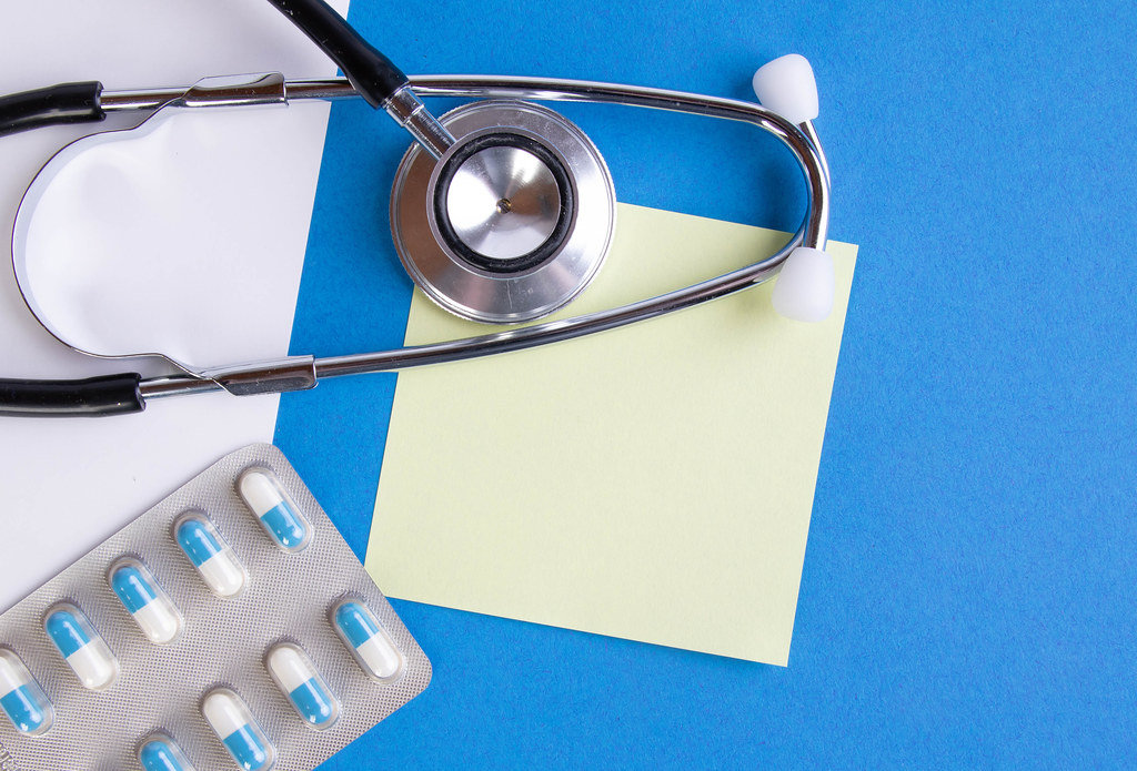 Stethoscope and pills on blue background with yellow empty note