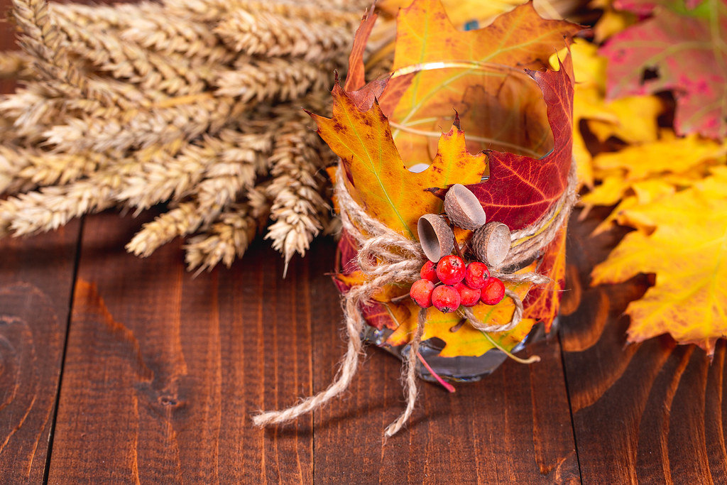 Original candlestick with autumn leaves and Rowan berries on a wooden background with wheat spikelets
