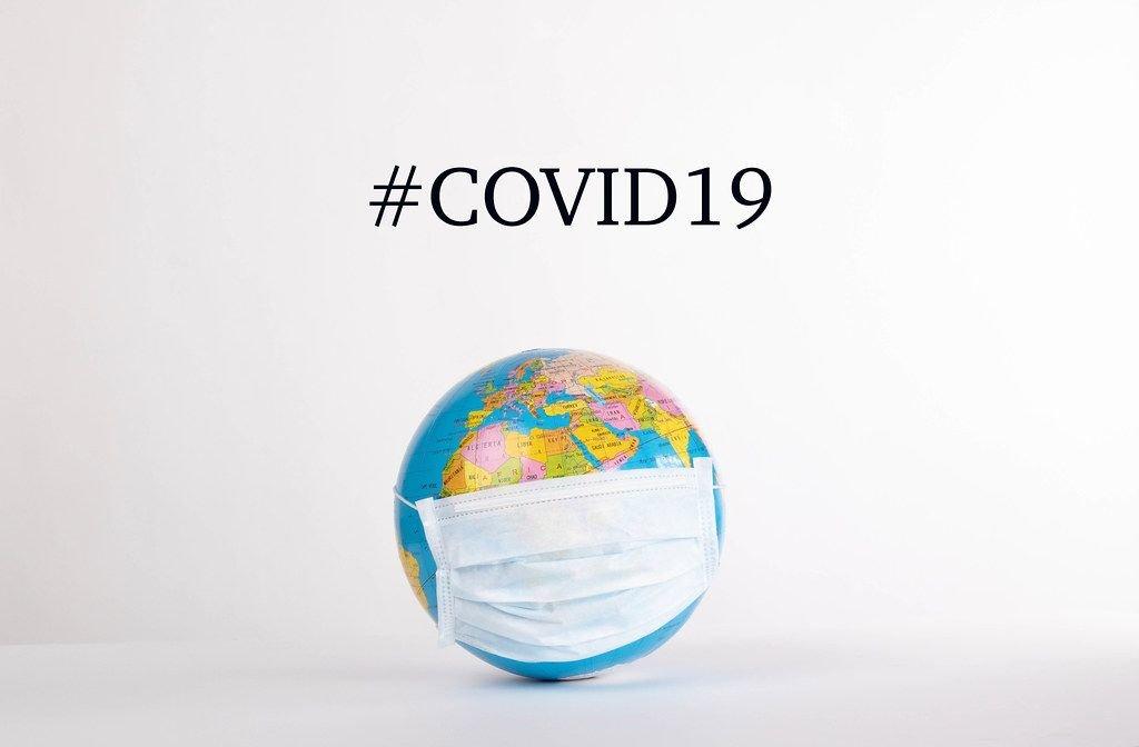 Globus mit Mundschutzmaske vor weißem Hintergrund mit #COVID19 Text
