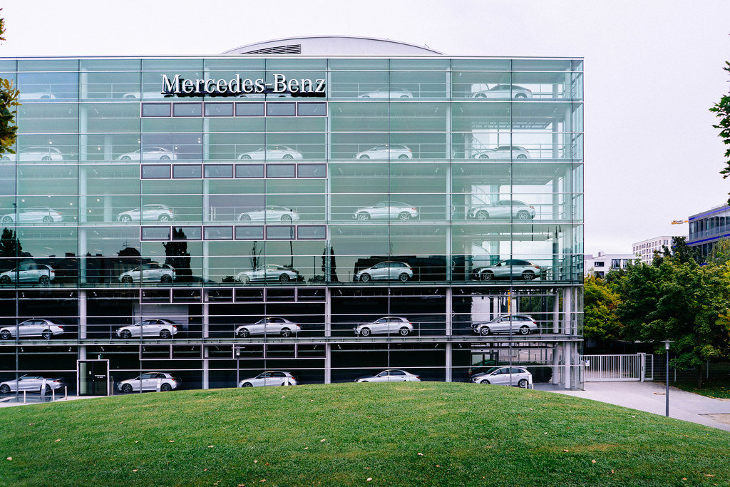 Multi-stories Mercedes-Benz glass showroom with silver cars in Munich, Germany